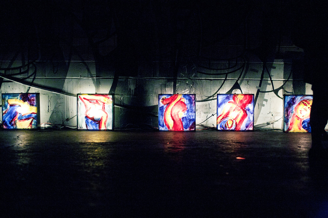Five lightboxes with paintings are lined up against a wall.